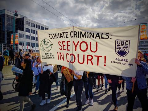 "People march along street, hold up sign reading ""Climate criminals: see you in court!"""