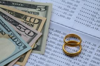 Wedding rings and money on top of a monthly bill