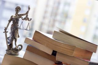 Lady Justice figure beside a pile of books