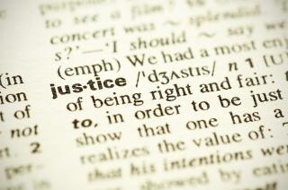 Close-up of the word justice in the dictionary
